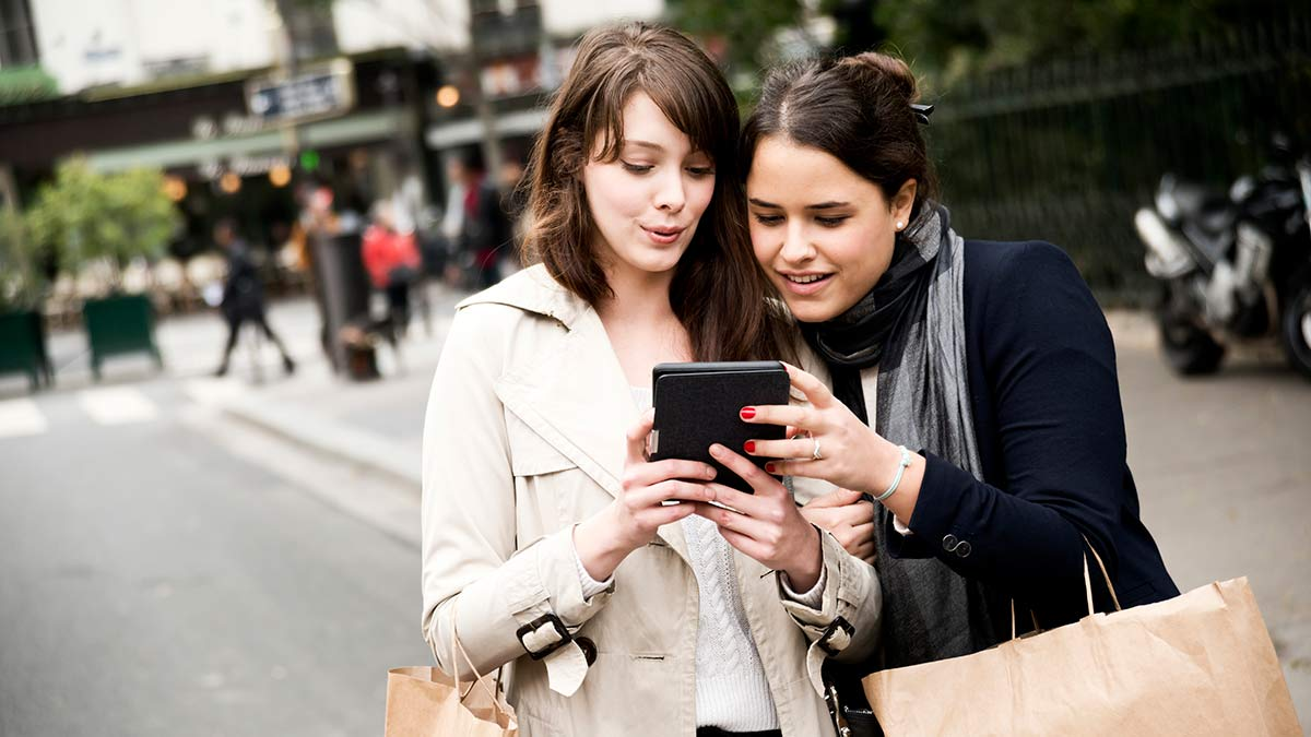 Two women looking at one mobile device
