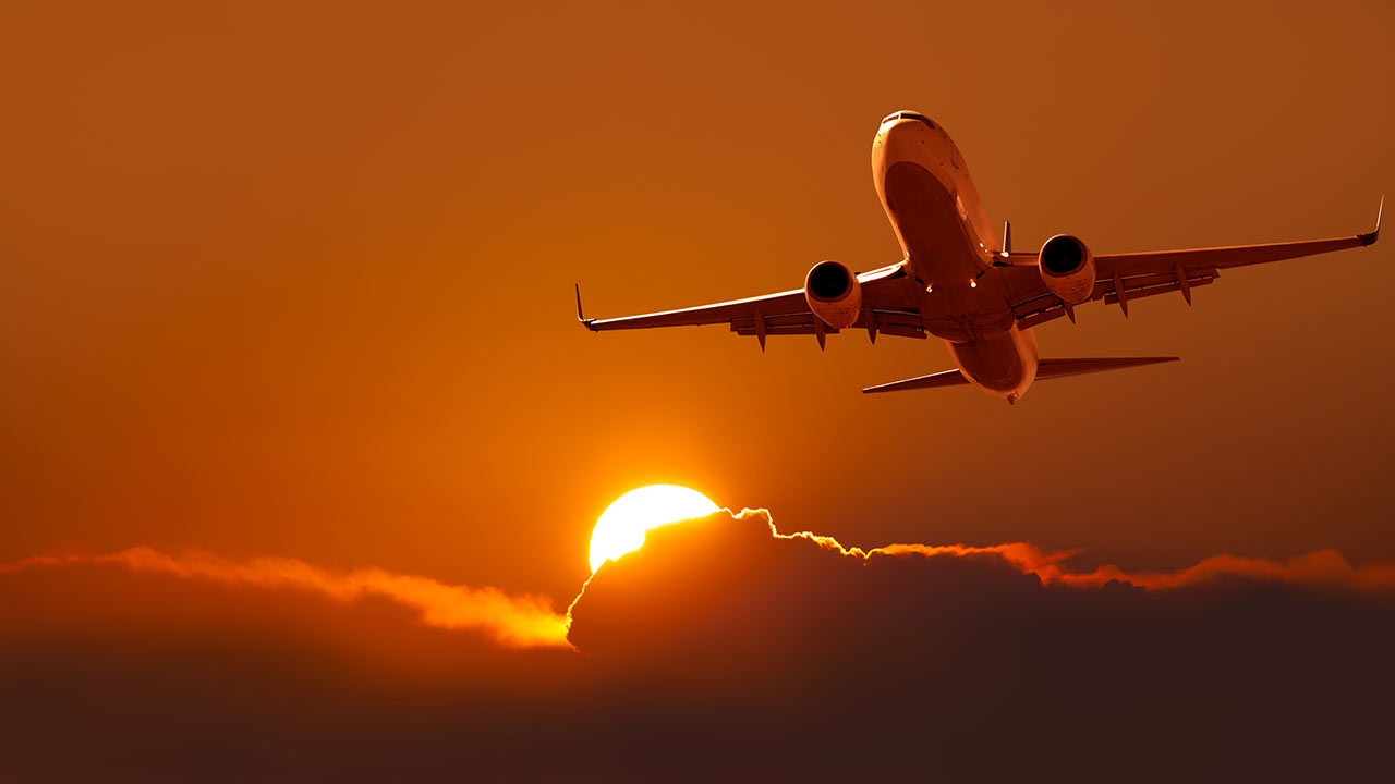 Airliner in sky at sunset